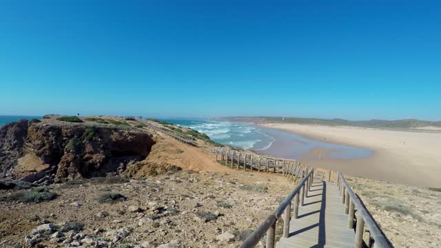 Point of view of walking on a boardwalk on the beach in Costa Vicentina, Sagres, Portugal.
