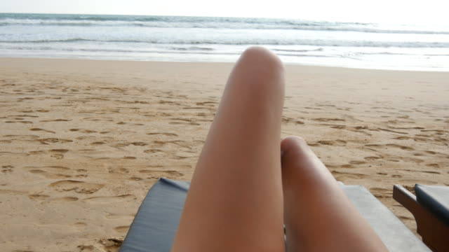 Point of view of young woman lying on sunbed by the sea and tanning. Female legs on chaise-longue relaxing and enjoying during summer vacation on ocean beach. Foot of girl on a resort. Close up Pov video
