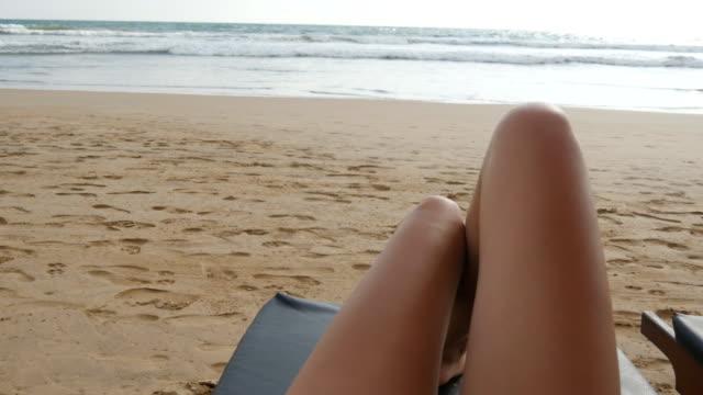 vídeos de stock, filmes e b-roll de ponto de vista da jovem mulher deitada na espreguiçadeira pelo mar e bronzeamento. pernas femininas na chaise-longue, relaxar e desfrutar durante as férias de verão na praia do oceano. pé de menina em um resort. close-up pov - perna termo anatômico