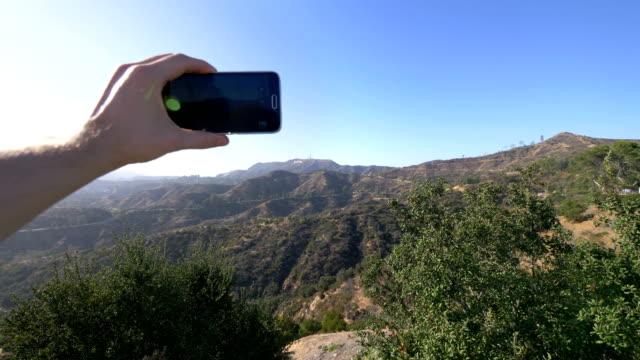 synpunkt på att ta en selfie på hollywood hills i los angeles i slow motion i 4k - hollywood sign bildbanksvideor och videomaterial från bakom kulisserna