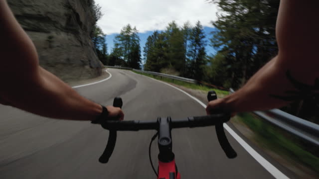 POV point of view racing bicycle riding on a road in the forest of Dolomites