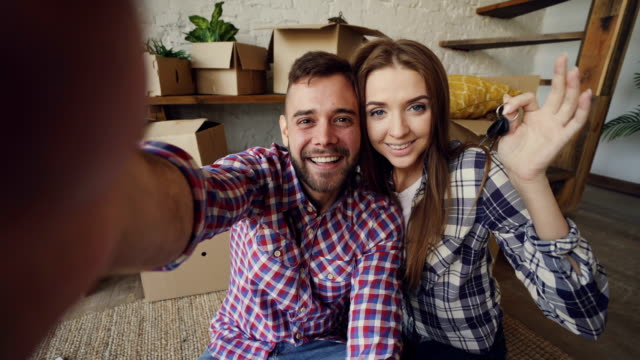 point of view shot of happy couple taking selfie with house keys after purchasing new apartment. young people are holding camera posing and kissing with boxes in background. - new home stock videos & royalty-free footage