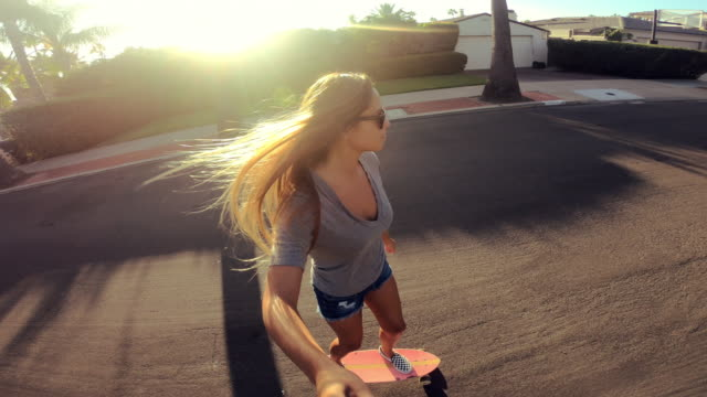 point of view shot of happy girl riding skateboard down street at sunset holding selfie camera - skateboarding stock videos and b-roll footage
