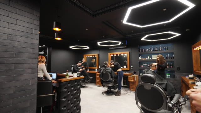Point of view shot of hipster barber throwing a hair cloak on the client with transition to black. Hairdresser puts on cape on camera in barber shop, POV. Trendy coiffeur at work in retro hair salon