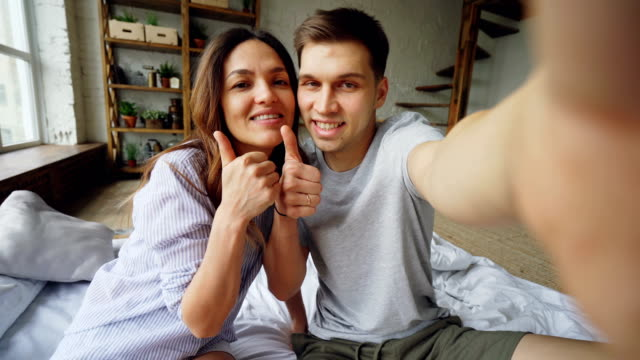 一緒にポーズをとって、キス、楽しみながら自宅のベッドの上に座って selfie を取って愛するカップルの視点ショット。モダンなインテリアと大きな窓が表示されます。 - セルフィー点の映像素材/bロール
