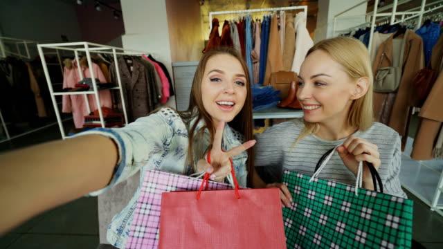 gesichtspunkt schuss von zwei attraktive sorglose mädchen selfie mit papiertüten in frauen kleider-shop machen. freunde sind posiert, lachen und glücklich im chat - achtlos stock-videos und b-roll-filmmaterial