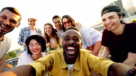 istock Point of view shot of young people multiethnic group taking selfie and holding camera, men and women are looking at camera, smiling and posing with drinks at rooftop party. 998913020