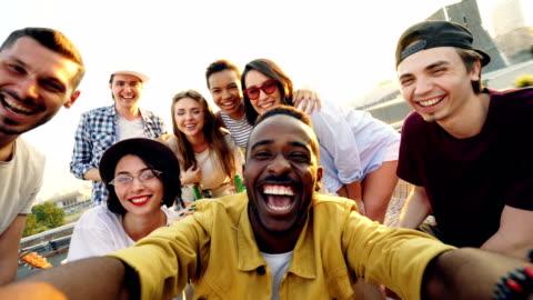 punto di vista girato di giovani gruppo multietnico che si fa selfie e tiene la macchina fotografica, uomini e donne guardano la macchina fotografica, sorridono e posano con bevande alla festa sul tetto. - people video stock e b–roll