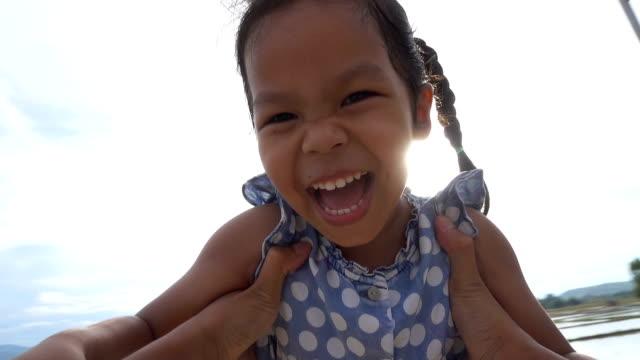 Oogpunt slow-motion shot van de vader zijn dochter rond in veld spinnen video
