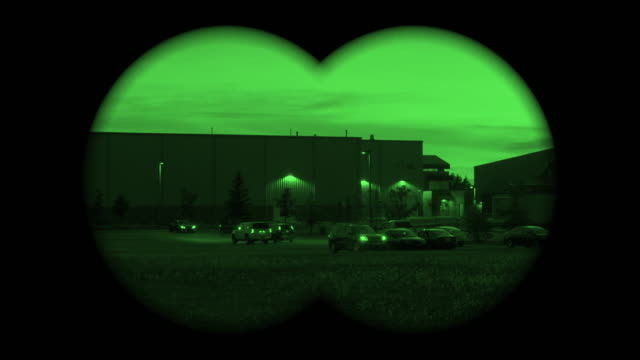 Point of View Through a Military Spy Binoculars on a parking lot