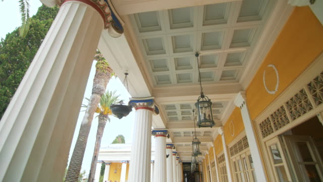 Point view lantern hanging on ceiling columns building with palm trees