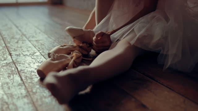尖った靴は脚に身を包み、バレリーナはリボンを結びます。クローズ アップ。 - バレエ点の映像素材/bロール