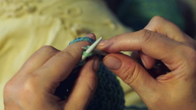 point-of-view of female fingers knit a scarf close up