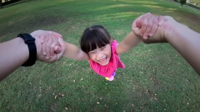 回転カメラで子供を浮かべて、公園での周り彼の若い娘の父の視点のショット - 身ぶり点の映像素材/bロール