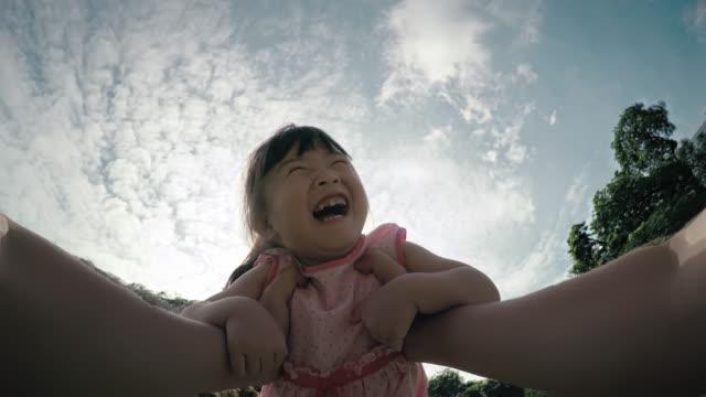Point-of-view shot van een vader die spinnen zijn jonge dochter, video