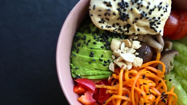 Poke bowl for healthy breakfast meal filmed in flat lay style directly from above in panoramic moving video clip.
