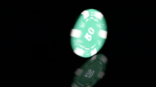 Poker Chips 50 turns on a black background. Slow motion video