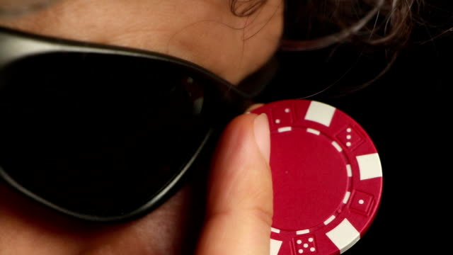 Poker player adjusting his sunglasses with a red chip video