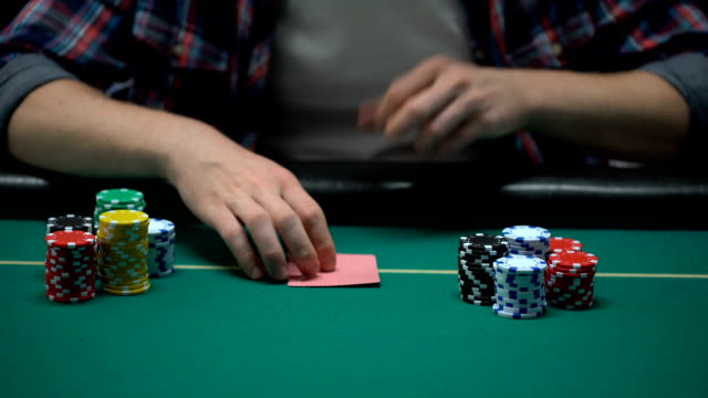 Poker player checking his cards and raising, putting dollars on table, all-in