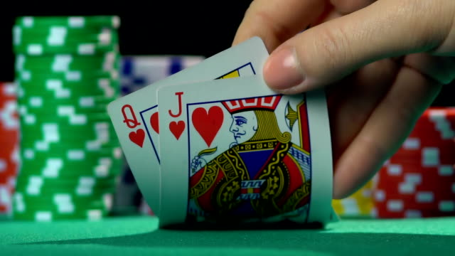 Poker player showing cards, queen and jack of hearts. Unequal video