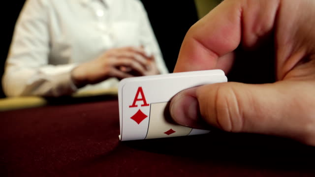 Poker player showing good card combination, ace and king on poker table. Man's hand close-up. Casino gamble.