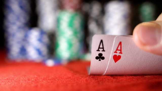Poker player showing good card combination, pair of aces in slow motion