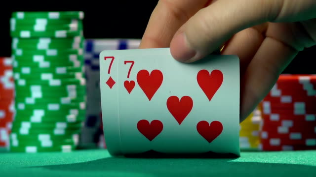 Poker player showing one pair of sevens, lucky number, winning video