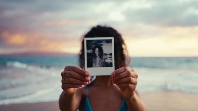 stockvideo's en b-roll-footage met polaroid portret van mooie jonge vrouw aan het strand bij zonsondergang - polaroid