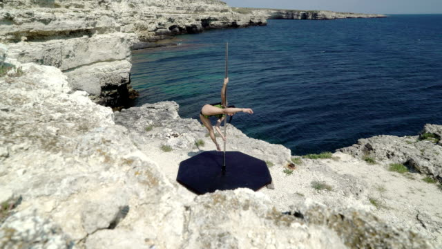 Pole dancer using portable pole fitness stage on rocky cliff by sea Pole dancer using portable pole fitness stage on rocky cliff by sea young woman performing acrobatic pole tricks during pole-dancing outdoor workout leotard stock videos & royalty-free footage