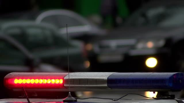 vídeos de stock, filmes e b-roll de um carro de polícia com um pisca-pisca, garante a proteção da ordem no lugar de uma reunião em massa de pessoas. luzes vermelhas e azuis piscam. as pessoas estão andando no fundo e carros estão indo. close-up - domínio
