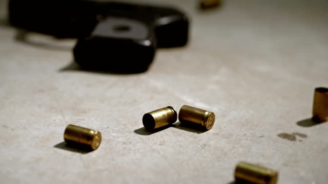 Police Crime Scene Handgun Bullets A small handgun with spent brass bullet casing on concrete. crime scene stock videos & royalty-free footage