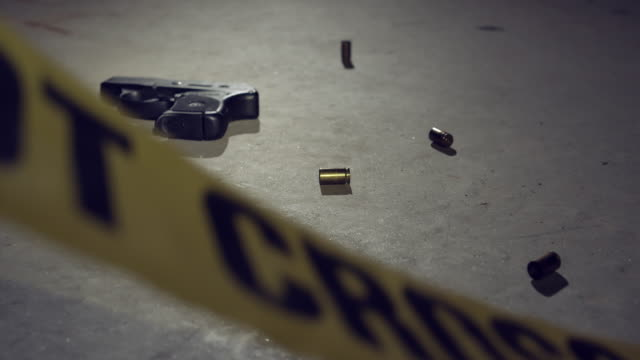 Police Crime Scene Tape with Handgun and Bullets A night crime scene with police tape handgun and bullets scattered on concrete floor. crime scene stock videos & royalty-free footage