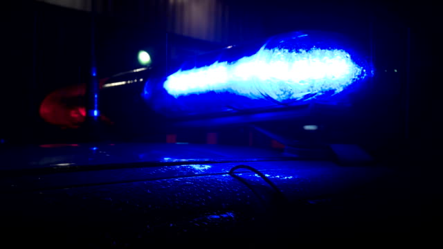Police lights flashing at night downtown at crime scene, close up. video