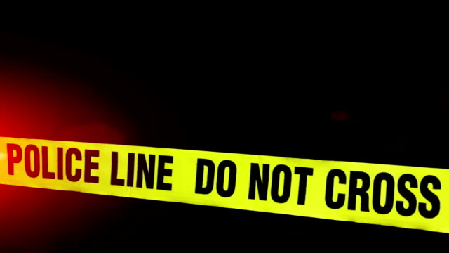 Police Line - Crime Scene Police line do not cross caution tape.  The crime scene has caution tape red and blue flashing police lights and fog. crime scene stock videos & royalty-free footage