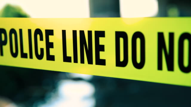 Police line do not cross cordon tape Video shoot of yellow police cordon tape tape stock videos & royalty-free footage