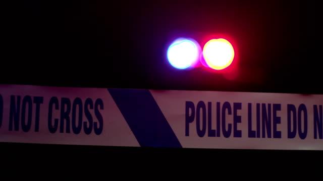 vídeos de stock e filmes b-roll de 4k dolly: police line tape with sirens behind - reino unido