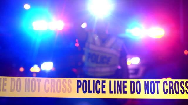 Police officer, emergency lights behind crime scene tape
