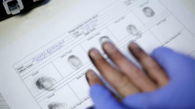 polis i examen handskar att ta fingeravtryck från misstänkt, händer närbild - kriminell bildbanksvideor och videomaterial från bakom kulisserna