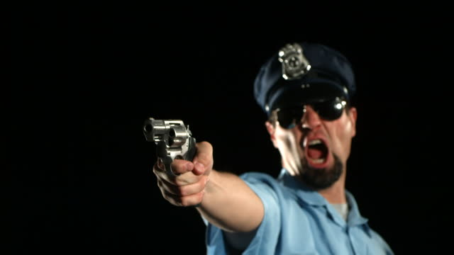 stockvideo's en b-roll-footage met police officer shoots gun, slow motion - gun shooting