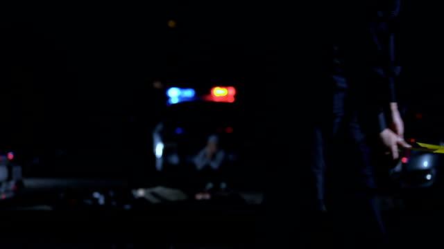 agente di polizia registra scena del crimine con nastro, luogo di indagine isolato - cadavere video stock e b–roll