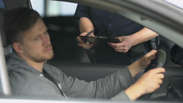 vídeos y material grabado en eventos de stock de oficial de policía escribiendo boleto a conductor masculino decepcionado, freno de reglas de tráfico - stop sign