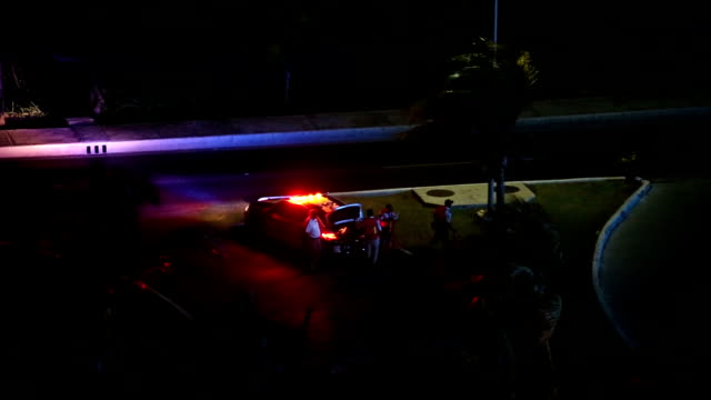 Police officers near car at night video