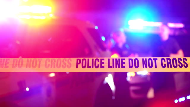 Police officers talking behind crime scene tape Crime scene tape in focus in the foreground. Police cars with emergency lights flashing, and officers talking out of focus in the background at night. crime scene stock videos & royalty-free footage
