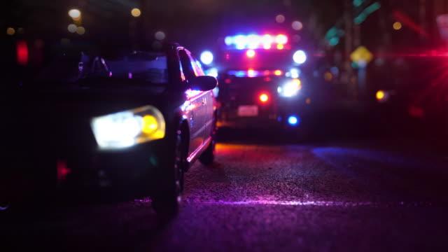 police patrol car at scene of emergency (optical lens defocus) - арест стоковые видео и кадры b-roll
