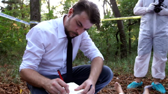 Police taking notes Two men, crime scene investigation, police and forensics doing their jobs, there is a dead body in the forest. detective stock videos & royalty-free footage