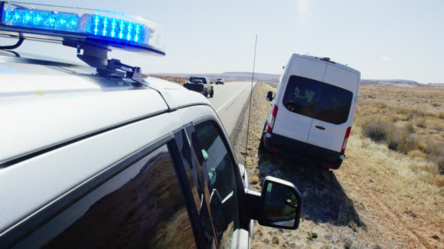 A Police Vehicle with Its Lights Pulls over a Large, White Van on the Side of the Highway/Interstate in the Deserts of Utah on a Bright, Sunny Day