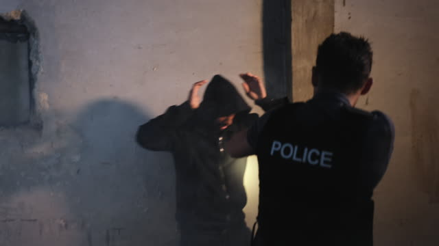 Policeman Arresting a Suspect in an Old Deserted House