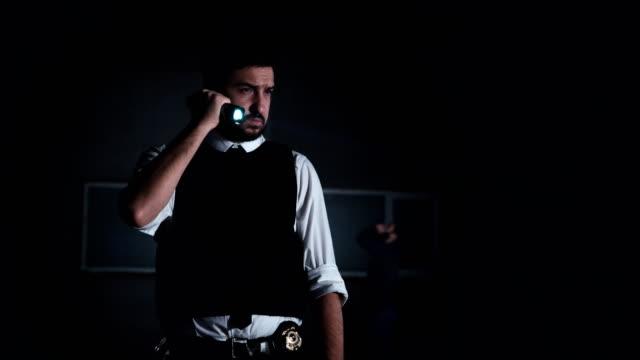 vídeos de stock e filmes b-roll de policeman finding evidence - lanterna elétrica