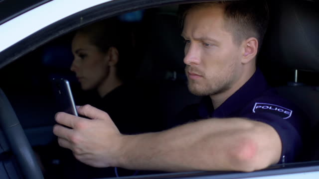poliziotto monitora le chiamate di emergenza al telefono mentre è seduto con il partner in auto - polizia video stock e b–roll