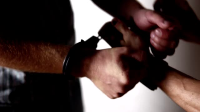 Policeman puts the handcuffs on the hands of criminal